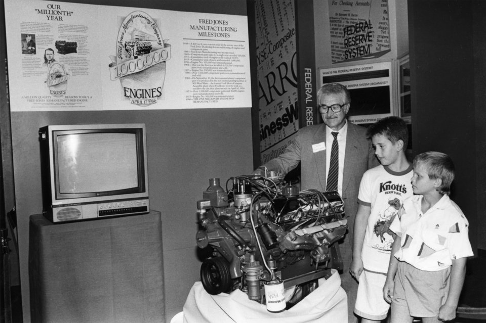 Photo - Chris Speligene shows visitors to Enterprise Square USA the millionth Ford engine remanufactured by Oklahoma City's Fred Jones Manufacturing Co. Looking at the engine, which was placed on exhibit in July 1987, are Chris McConnell, 10, and Justin Wenzel, 10.    Oklahoman Archives Photo  STAFF PHOTO -  STAFF PHOTOGRAPHER