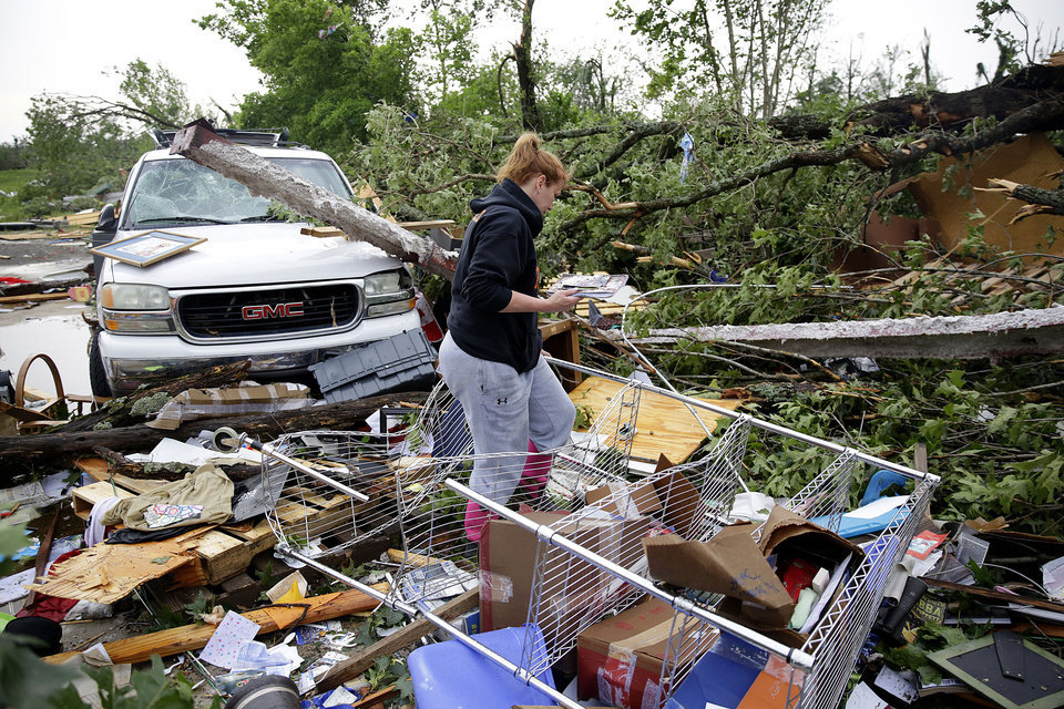 Photo - Michelle Underwood searches through the wreckage of a feed store in Peggs, Okla., where she stored most of her belongings Tuesday, May 21, 2019. An apparent tornado hit the area Monday night. (Mike Simos/Tulsa World via AP)