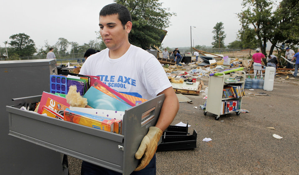 Photo - Senior C.J. Ciulla carries some books rescued from the debris of portable classroom  at Little Axe School, Tuesday, May 11, 2010. The school was hit by a tornado Monday, May 10, 2010. Photo by David McDaniel, The Oklahoman