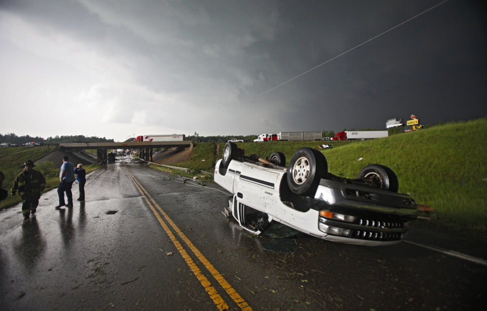 Photo - A car lies on its top after it was flipped when a tornado damaged the area around I-40 and Choctaw Road on Monday, May 10, 2010, in Oklahoma City, Okla.  Photo by Chris Landsberger, The Oklahoman