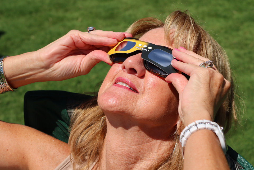 Photo -  Janet Owen came to watch the eclipse with her sister Monday as part of her birthday celebration at the Myriad Botanical Gardens. [Photo by Doug Hoke, The Oklahoman]