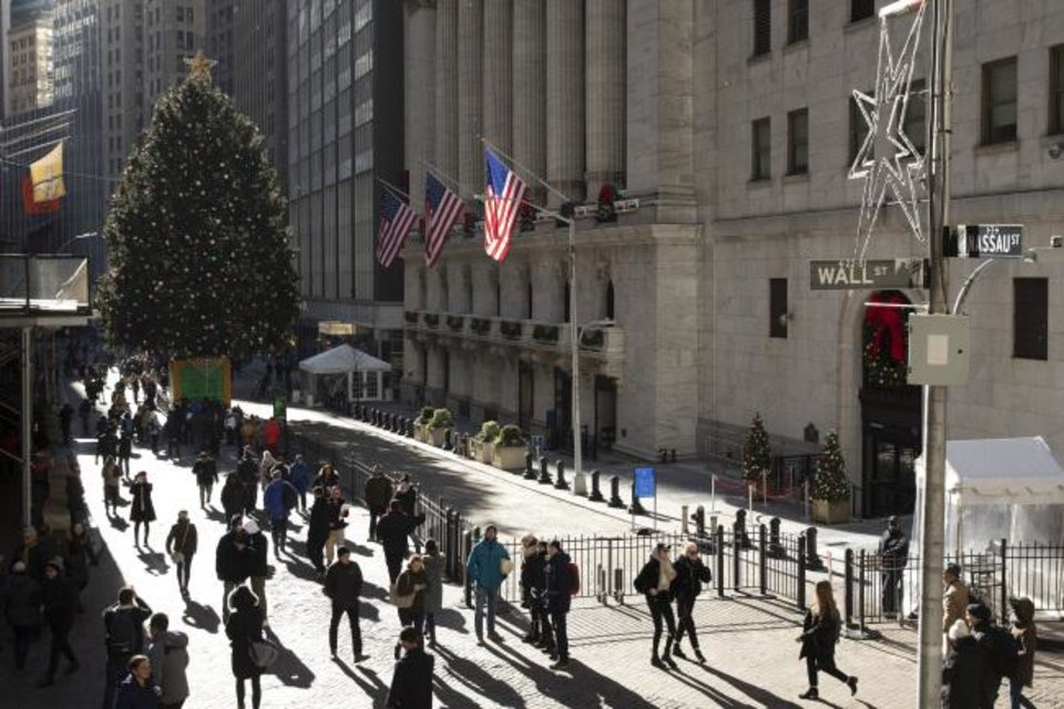 Photo -  People walk by the New York Stock Exchange. [AP PHOTO]