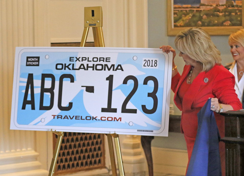 Photo -  Gov. Mary Fallin unveils the new design for the state's license plate Monday at the state Capitol in Oklahoma City. [Photo By Steve Gooch, The Oklahoman]