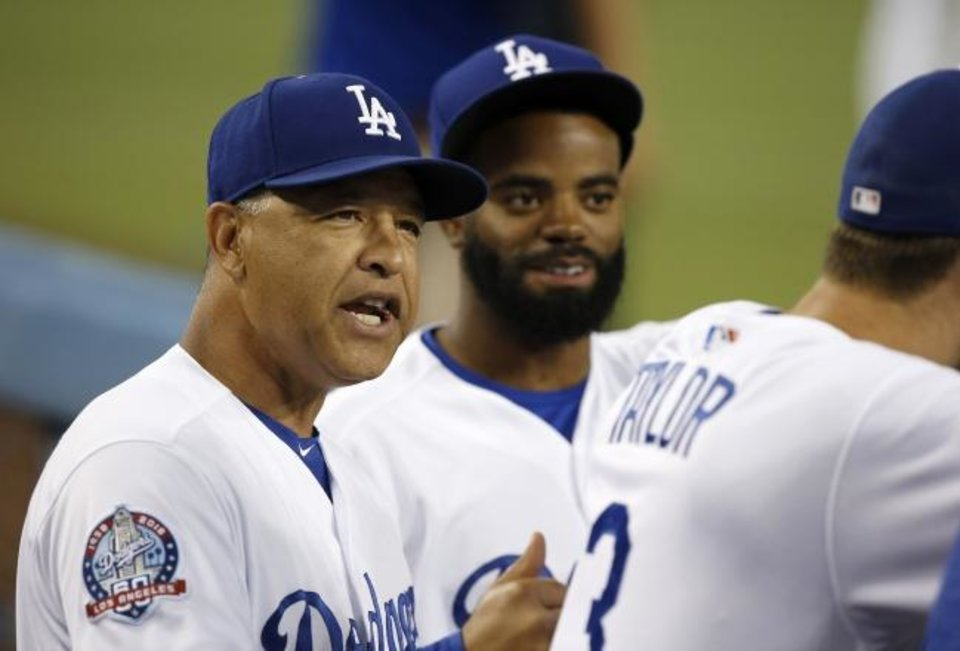 Photo -  Los Angeles Dodgers manager Dave Roberts, left, talks to Chris Taylor with Andrew Toles, center, listening before a game against the San Diego Padres on Sept. 21, 2018. [AP Photo/Alex Gallardo]