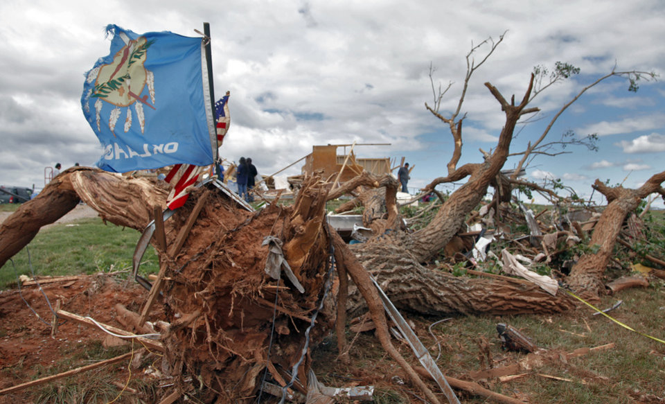 Photo - A tattered Oklahoma flag waves outside the home of Charles and Susan Sleeper where there home was destroyed by Tuesday's tornado west of El Reno, Wednesday, May 25, 2011. Photo by Chris Landsberger, The Oklahoman