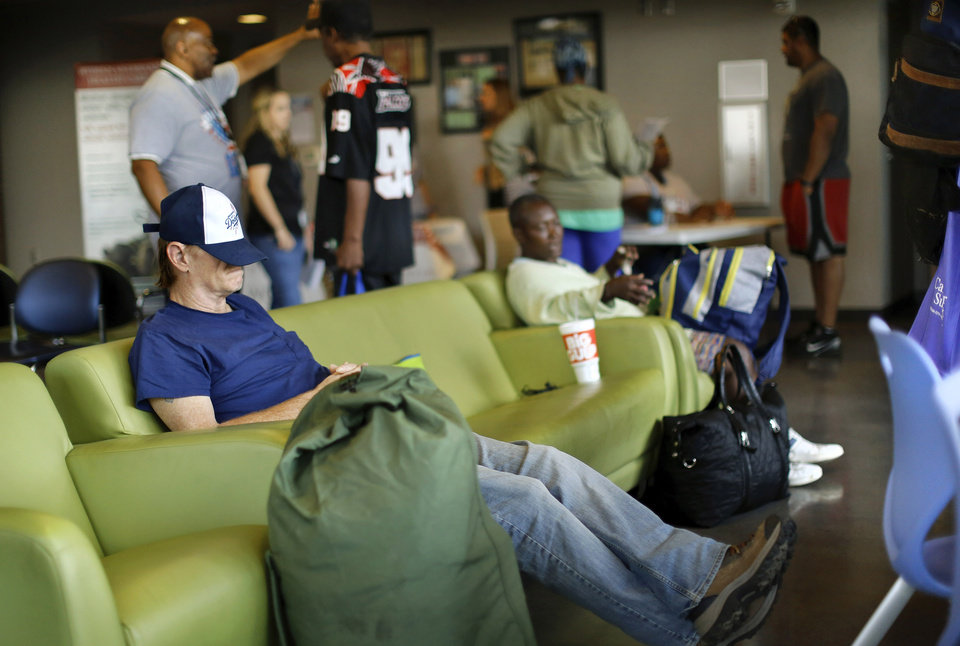 Photo -  A veteran rests on a sofa while waiting to fill out papers at the Sooner Stand Down for homeless veterans on Friday at the Homeless Alliance's WestTown Homeless Resource Campus in Oklahoma City. [Photo by Jim Beckel, The Oklahoman]