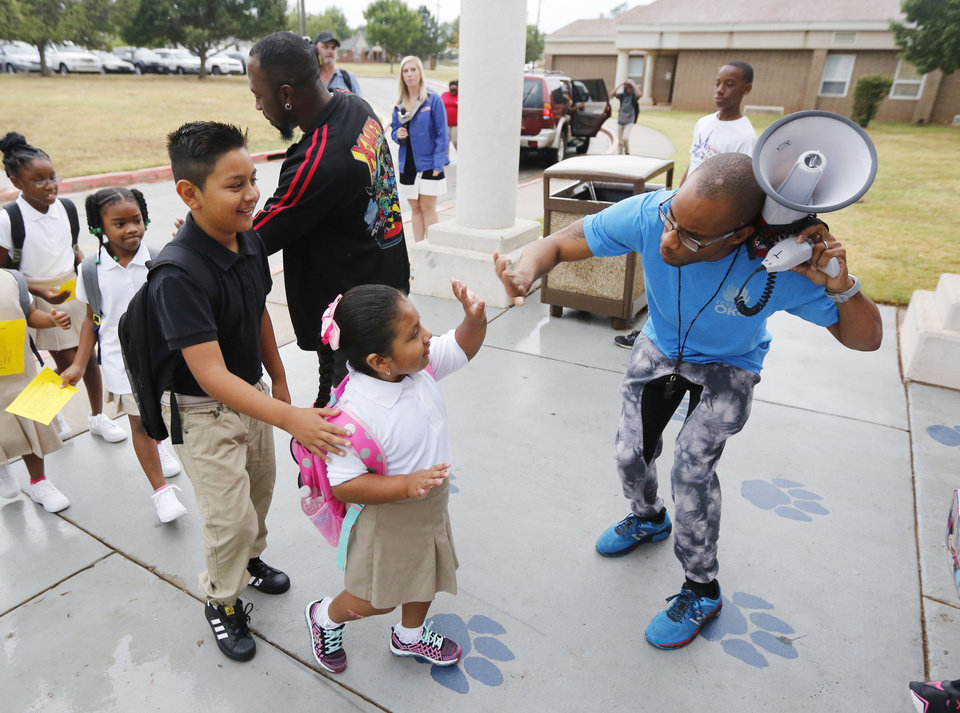 Photo - Volunteer Ernest Odunze gives high-fives to all the children at the beginning of the first day of school at Thelma Parks Elementary School in Oklahoma City, Okla. Tuesday, Aug. 1, 2017.  Photo by Paul Hellstern, The Oklahoman