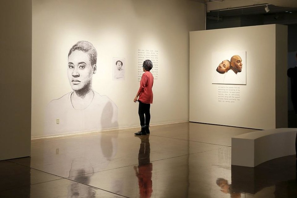 Photo - A person looks at an exhibit by artist Tatyana Fazlalizadeh, titled