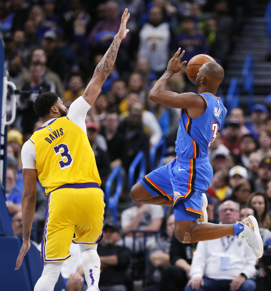 Photo - Oklahoma City's Chris Paul (3) shoots as Los Angeles' Anthony Davis (3) defends in the fourth quarter during an NBA basketball game between the Oklahoma City Thunder and the Los Angeles Lakers at Chesapeake Energy Arena in Oklahoma City, Friday, Nov. 22, 2019. The Lakers won 130-127. [Nate Billings/The Oklahoman]