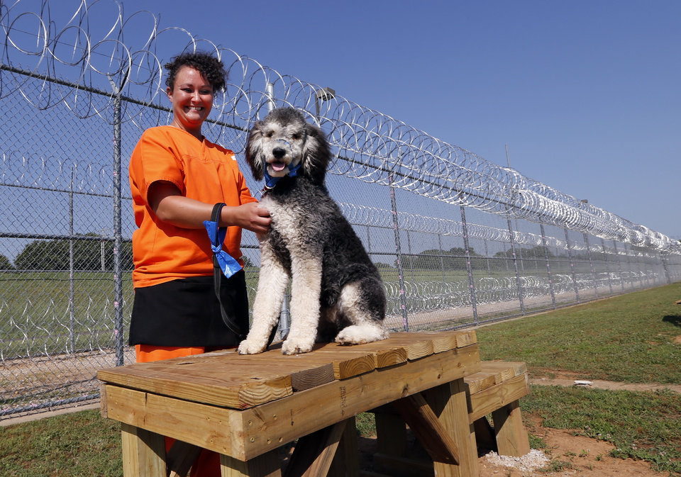 Photo -  Lacey Wallace works with McAlister at the opening of a new dog training facility. The building and grounds allow inmates to train dogs that may be owned but unruly or are homeless and in need of socialization. [Photo by Steve Sisney, The Oklahoman]