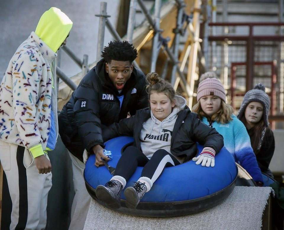 Photo - Oklahoma City Thunder player Shai Gilgeous-Alexander helps a rider get started down a slope next to Darius Bazley, left, during a visit by Thunder basketball players to the LifeShare WinterFest at Chickasaw Bricktown Ballpark in Oklahoma City, Monday, Dec. 30, 2019. [The Oklahoman Archives]