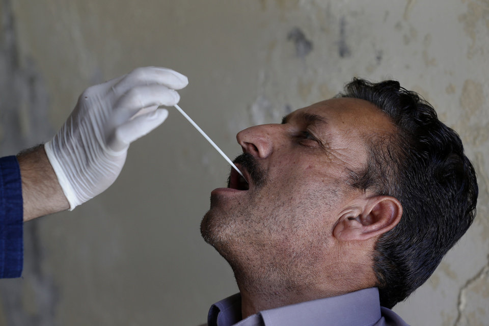 Photo -  FILE - In this June 15, 2020, file photo, a health worker takes a nasal swab sample of a person during a door-to-door testing and screening facility for the new coronavirus, in Islamabad, Pakistan. Pakistan ranks among countries hardest hit by the coronavirus with infections soaring beyond 18,000, while the government, which has opened up the country hoping to salvage a near collapsed economy, warns a stunning 1.2 million Pakistanis could be infected by the end of August. (AP Photo/Anjum Naveed, File)