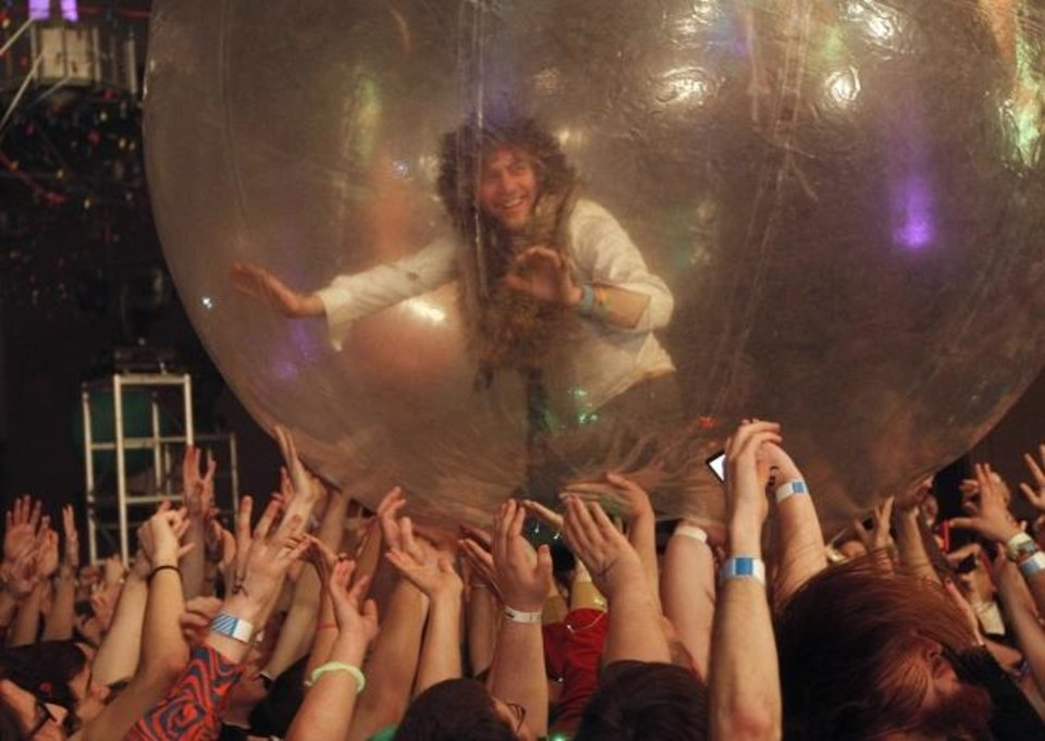 Photo -  Wayne Coyne, of the Flaming Lips, rolls around the crowd in his