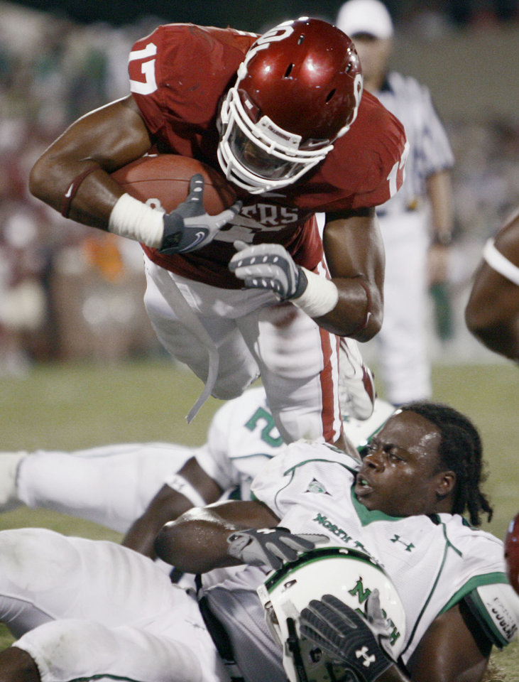 Photo - Oklahoma running back Mossis Madu (17) dives over North Texas linebacker Brandon Monroe (4) into the endzone for a touchdown in the second half during the University of Oklahoma Sooners (OU) college football game against the University of North Texas Mean Green (UNT) at the Gaylord Family - Oklahoma Memorial Stadium, on Saturday, Sept. 1, 2007, in Norman, Okla.
