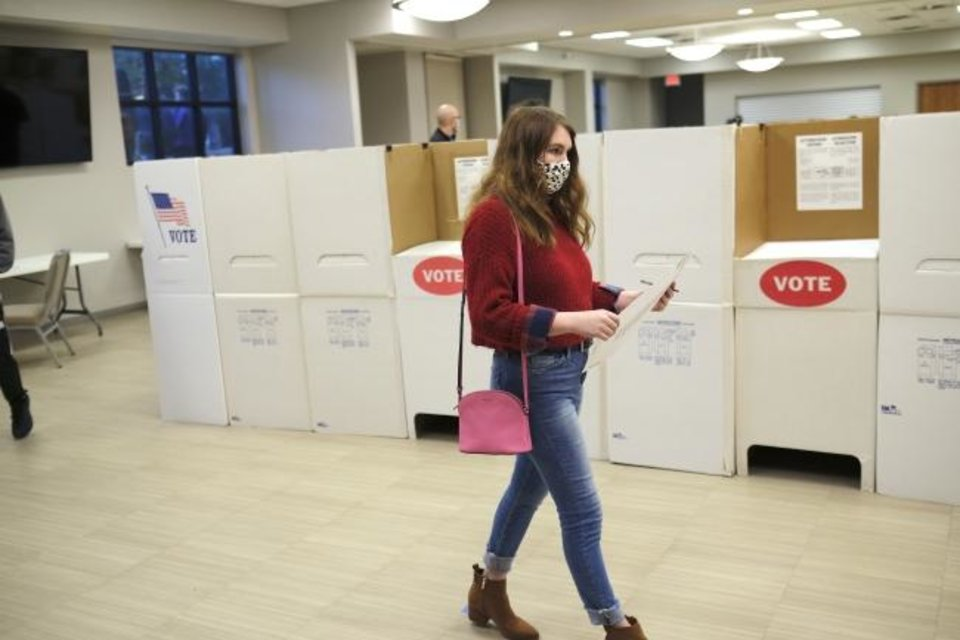 Photo -  Michyla Armstrong carries her completed ballot to the voting machine. First-time voter, Michyla Armstrong, voted early at the Edmond Church of Christ, Friday, October 30, 2020. [Doug Hoke/The Oklahoman]
