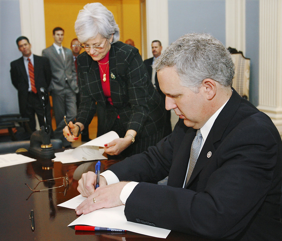 Photo - Oklahoma Gov. Brad Henry adds his signature to documents as Secretary of State Susan Savage signs and seals them when Oklahoma's electors met at the state Capitol Monday, Dec. 15, 2008, to cast the state's official ballots for the 2008 presidential election.  ORG XMIT: KOD