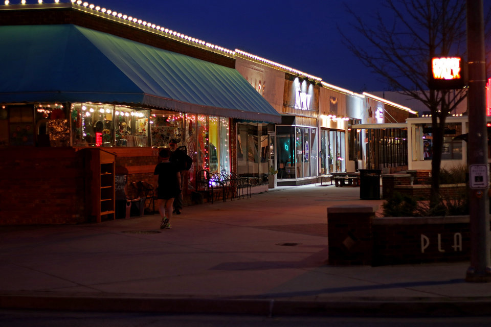 Photo - The Plaza District, usually crowded on a Friday night, is bare because of the stay-at-home orders issued my Mayor Holt and Governor Stitt to combat the spread of the COVID-19 virus. Friday, March 27, 2020.  [Photo by Doug Hoke/The Oklahoman]