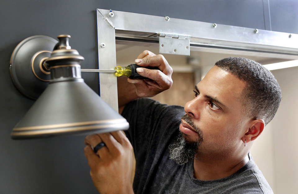 Photo -  D&D Custom Built Food Trucks owner Deion Estrada screws in a lamp on a food truck at his shop recently.