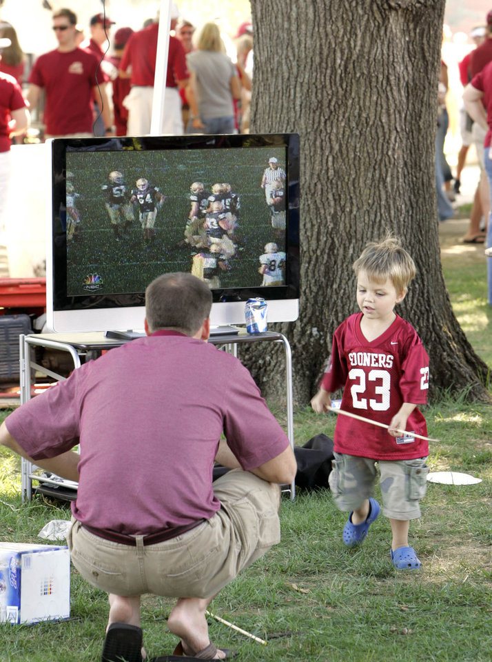 Photo - Mike Beckham of Norman, watchs football on a large screen, along with Logan McGrath, 3, of Norman, during a tailgate party prior to  the University of Oklahoma Sooners (OU) college football game against the University of North Texas Mean Green (UNT) at the Gaylord Family - Oklahoma Memorial Stadium, on Saturday, Sept. 1, 2007, in Norman, Okla.