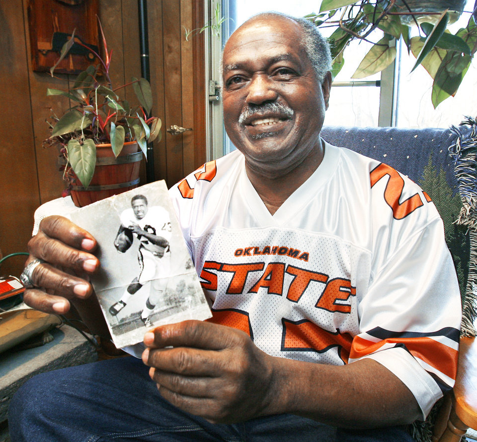 Photo - Former Oklahoma State player Chester Pittman holds a photo from his playing days in Stillwater. Photos by Steve Sisney, The Oklahoman
