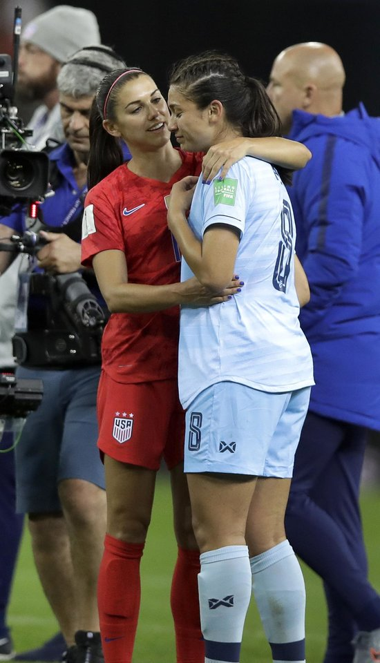 Photo -  United States' Alex Morgan, left, comforts Thailand's Miranda Nild, right, after the Women's World Cup Group F soccer match between United States and Thailand at the Stade Auguste-Delaune in Reims, France, Tuesday, June 11, 2019. Morgan scored five goals during the match. (AP Photo/Alessandra Tarantino)