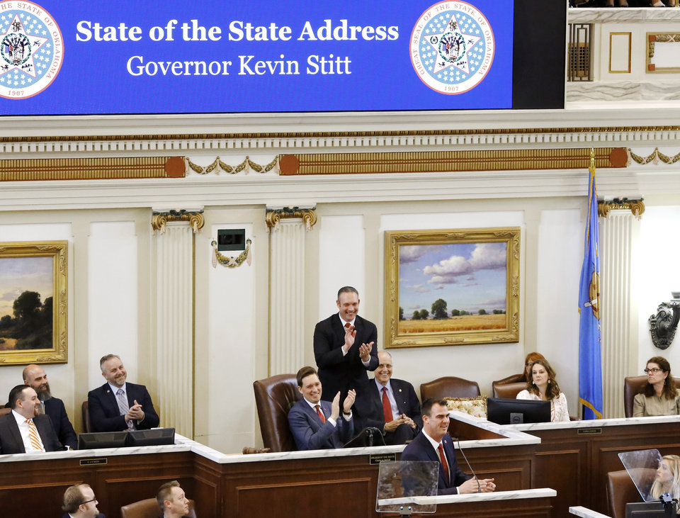 Photo - Okla. Gov. Kevin Stitt, standing at podium, receives applause while in the House chamber to deliver his first State-of-the-State message to a joint session of the Legislature at the Capitol on Monday, Feb. 4, 2019. Behind the new governor are Lt. Gov. Matt Pinnell, Speaker Charles McCall, standing, and Speaker Pro-Tempore Harold Wright. In his address, Stitt told lawmakers that teachers deserve another pay raise and asked them to find the money to fund it. The new Republican governor also used the speech to outline his vision for an economy-focused administration that will produce an efficient and adaptive state government.  Photo by Jim Beckel, The Oklahoman.