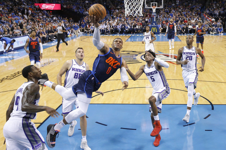 Photo - Oklahoma City's Russell Westbrook (0) goes to the basket between Sacramento's Iman Shumpert (9), Nemanja Bjelica (88) and De'Aaron Fox (5) during an NBA basketball game between the Oklahoma City Thunder and the Sacramento Kings at Chesapeake Energy Arena in Oklahoma City, Sunday, Oct. 21, 2018. Photo by Bryan Terry, The Oklahoman