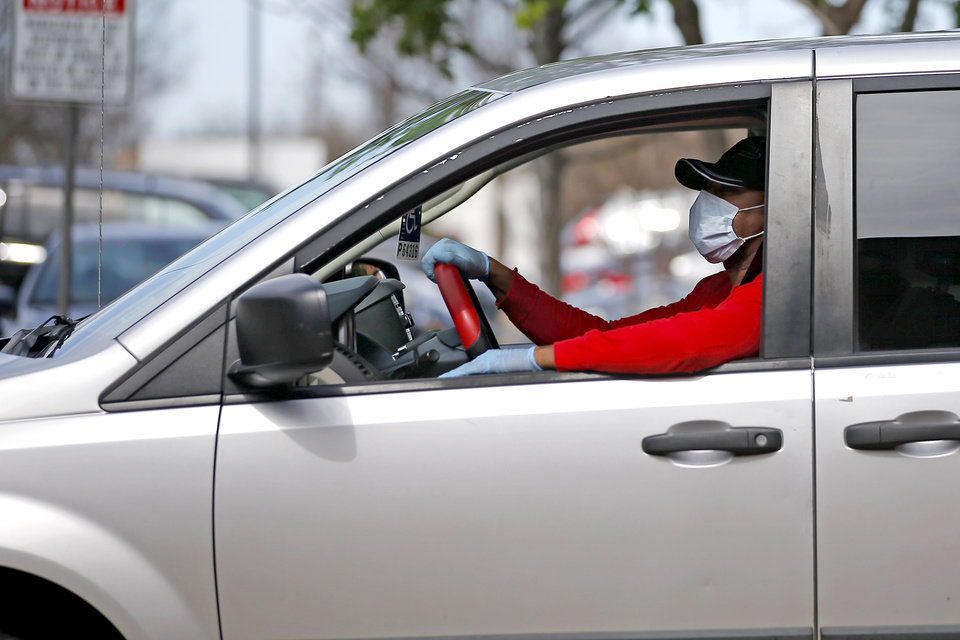 Photo - A person wears a mask as they drive away from Integris Baptist Medical Center in Oklahoma City, Wednesday, March 18, 2020. [Bryan Terry/The Oklahoman]