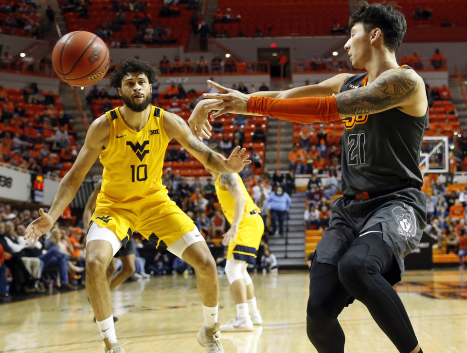 Photo - Oklahoma State's Lindy Waters III (21) passes away from West Virginia's Jermaine Haley (10) in the second half during a men's college basketball game between the Oklahoma State Cowboys and West Virginia Mountaineers at Gallagher-Iba Arena in Stillwater, Okla., Monday, Jan. 6, 2020. West Virginia won 55-41. [Nate Billings/The Oklahoman]