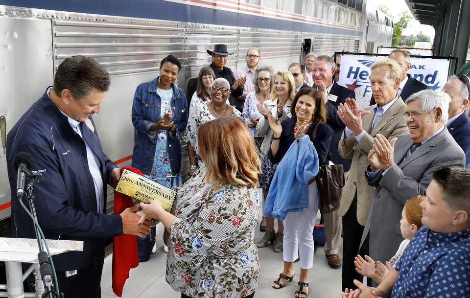 "Photo - Katie Moore accepts  the ""golden ticket"" and a souvenir shirt from Tim Gatz during a ceremony commemorating the 20th anniversary  of the return of passenger rail service to Oklahoma at Santa Fe Depot in downtown Oklahoma City Friday morning, June 14, 2019. The Heartland Flyer is celebrating its 20th year of serving passengers in Oklahoma and Texas.  Gatz is the state's secretary of transportation and serves as executive director of the Oklahoma Department of Transportation. Moore, of Oklahoma City, was honored  as being the person who suggested the name, Heartland Flyer, in 1999 when she was 11 years old. Her family attended the event with her. The Heartland Flyer, which runs daily, has carried more than 1.4 million passengers between Oklahoma City and Fort Worth during the past two decades. Originating its route on Oklahoma City, the Heartland Flyer connects to the Texas Eagle train in Fort Worth, which provides service to major cities including Dallas, Little Rock, St. Louis or Austin and San Antonio. [Jim Beckel/The Oklahoman]"