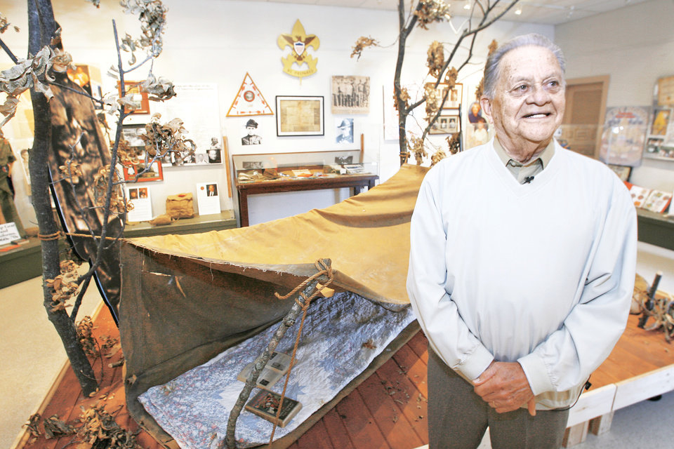 Photo - Jack Shoemate, a member of the Board of Directors of the Osage County Historical Museum in Pawhuska, is shown recently at the museum's display on the first Boy Scout Troop in America. PHOTO BY DAVID MCDANIEL, THE OKLAHOMAN