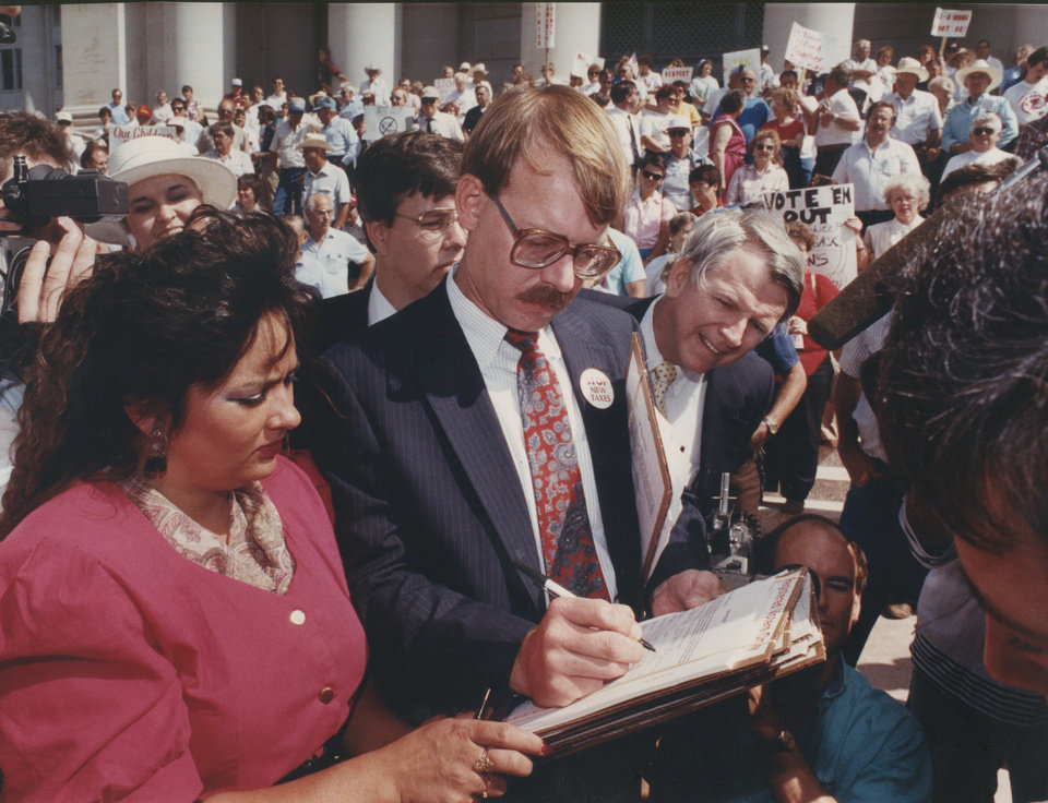 Photo - On May 25, 1990, Lori Anne Horner watched Dan Brown, chairman of STOP New Taxes, put the first signature on a petition calling for the repeal of a $223 million tax increase. [Photo by Steve Sisney, The Oklahoman Archives]