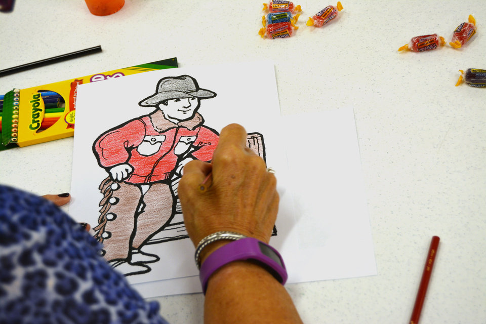 A Workshop Participant Applies Color To An Image At Coloring Book Session For Adults In