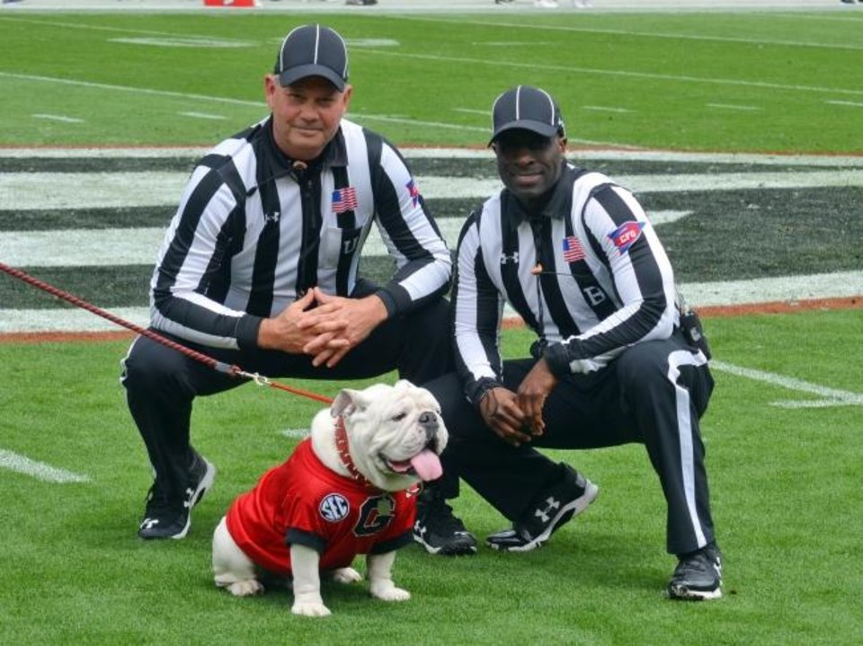 Photo -  There are some perks of being a college football official. Phillip Davenport, left, and Grantis Bell pose with Georgia mascot Uga. [Gary McGriff via AP]