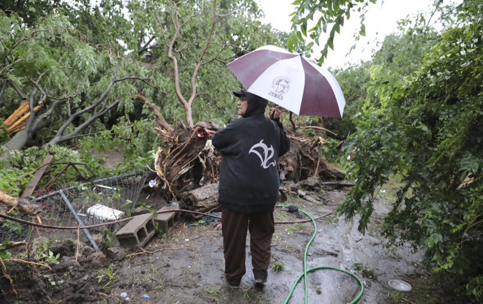 Photo - Carmen Perez surveys storm damage of her home near Marshall and North Rockford in Tulsa, Okla., on Tuesday, May 21, 2019. Their front door was blocked by a tree and they had to get out of their home through a front window.  (Tom Gilbert/Tulsa World via AP)
