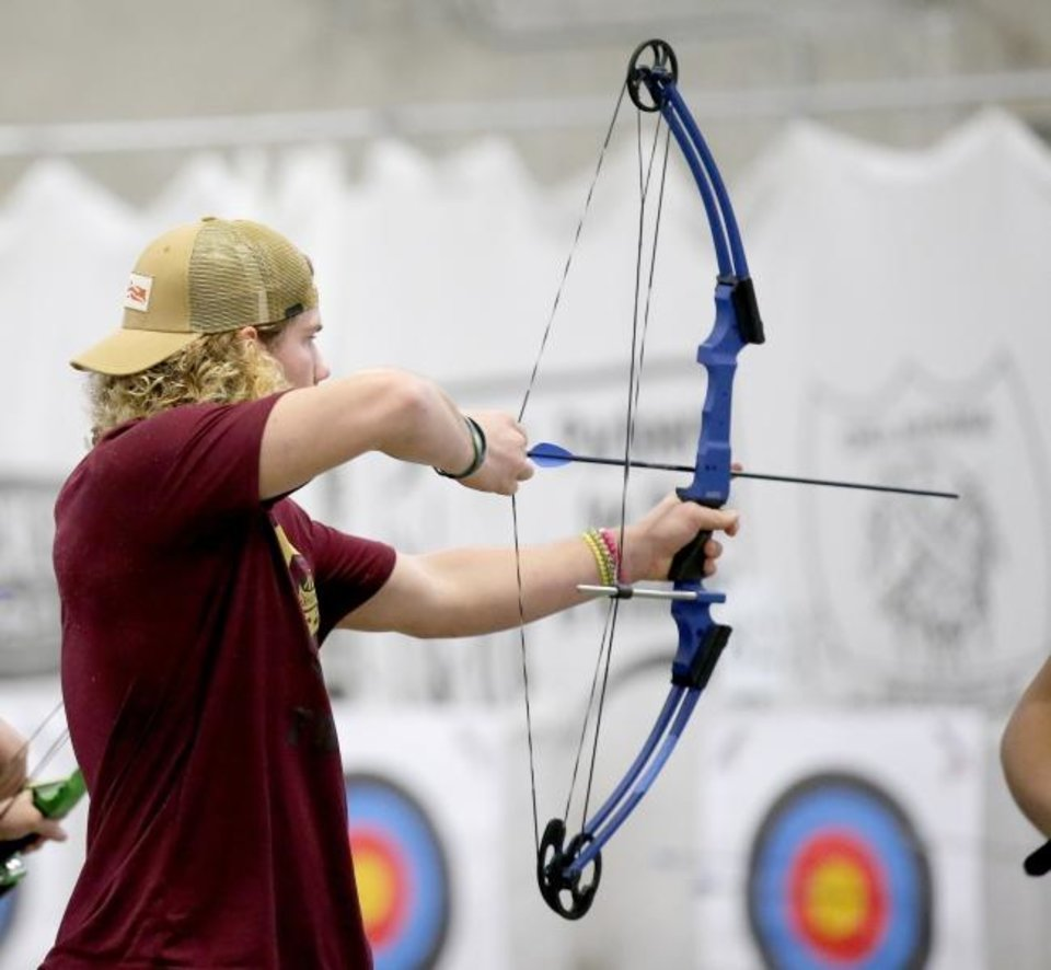 Photo -  Brexton Green, junior at Cashion, shoots Wednesday during the Western Tier 2 Archery in the Schools Program state shoot in The Pavilion at the OKC State Fair Park. [SARAH PHIPPS/THE OKLAHOMAN]