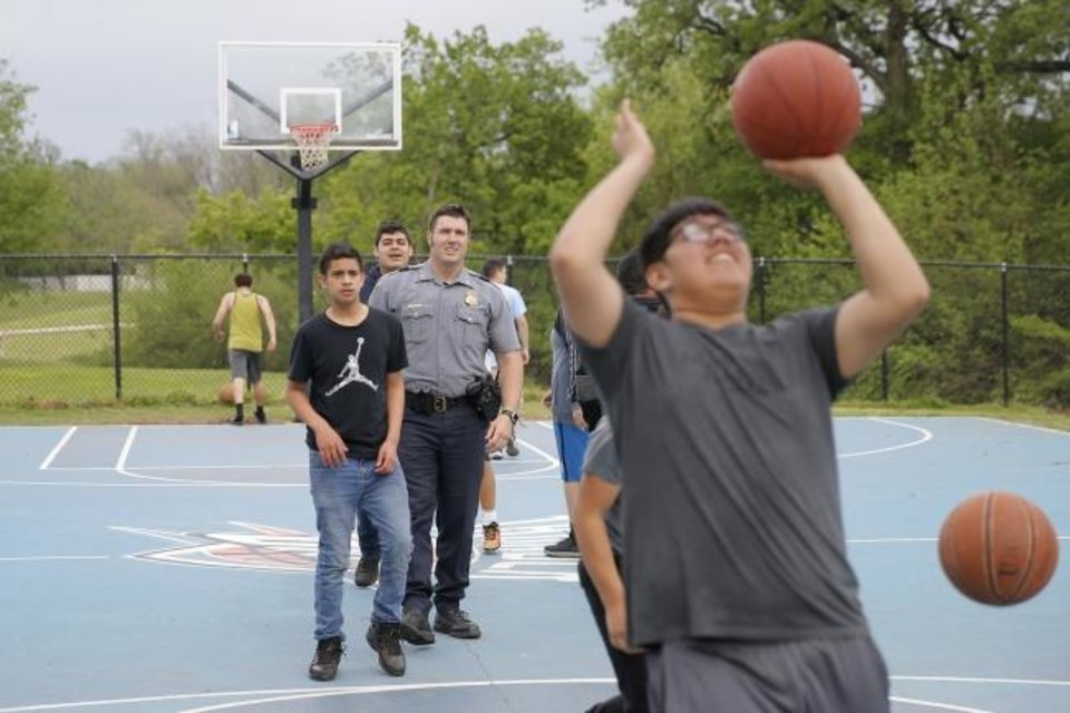 Photo -  Sgt. Jordan Wacker plays basketball with youth during the Police Athletic League's after-school program. [Bryan Terry/The Oklahoman]