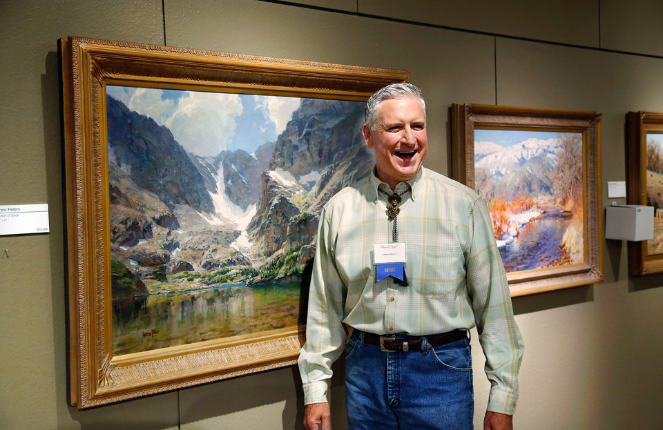 "Photo - Iowa artist Andrew Peters smiles as he poses with his oil painting, ""The Lake of Glass,"" after he and the artwork were honored as this year's Prix de West winner at the National Cowboy and Western Heritage Museum on Saturday, June 13, 2015. Peters, 60, from Council Bluffs, used a setting in Rocky Mountain National Park as the inspiration for his 30"" x 40' piece of art. Photo by Jim Beckel, The Oklahoman."
