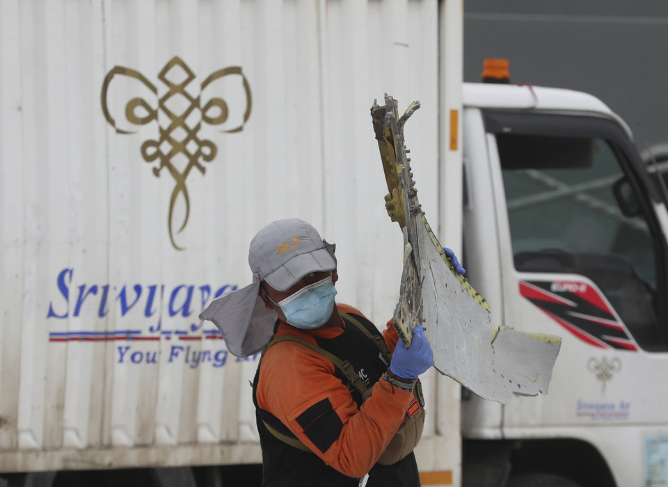 Photo -  Rescuers carry debris found in the waters around the location where Sriwijaya Air passenger jet crashed at Tanjung Priok Port in Jakarta, Indonesia, Monday, Jan. 11, 2021. The search for the black boxes of a crashed Sriwijaya Air jet intensified Monday to boost the investigation into what caused the plane carrying dozens of people to nosedive at high velocity into the Java Sea. (AP Photo/Achmad Ibrahim)