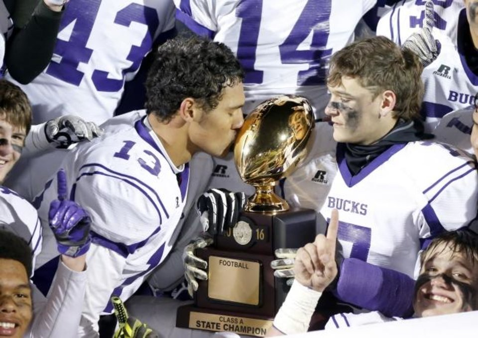 Photo -  Hominy's Zaven Collins (13) kisses the Class A state football championship trophy beside Colt Wilson after winning the 2016 title over Wynnewood. [Bryan Terry/The Oklahoman]