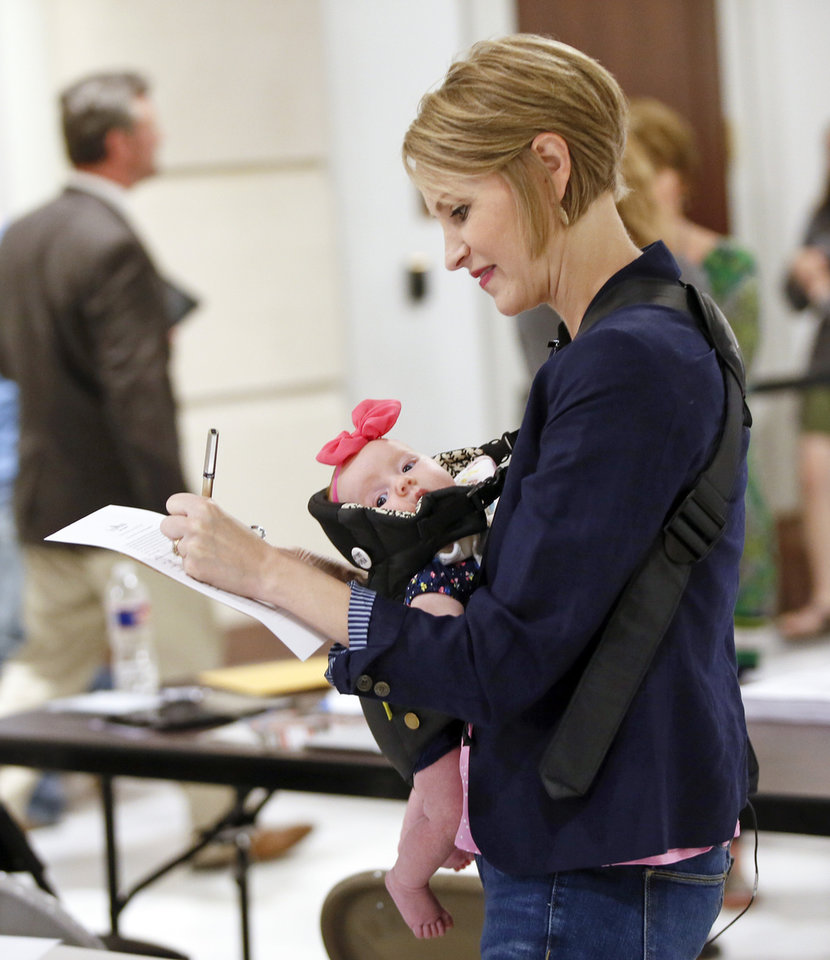 Photo -  Carri Hicks, a fourth-grade teacher at Deer Creek's Grove Valley Elementary School, fills out a form with 2-month-old daughter Cami Hicks to run for the District 40 Senate seat as a Democrat during candidate filing on the 10th day of a walkout by Oklahoma teachers in Oklahoma City. [Photo by Nate Billings, The Oklahoman]