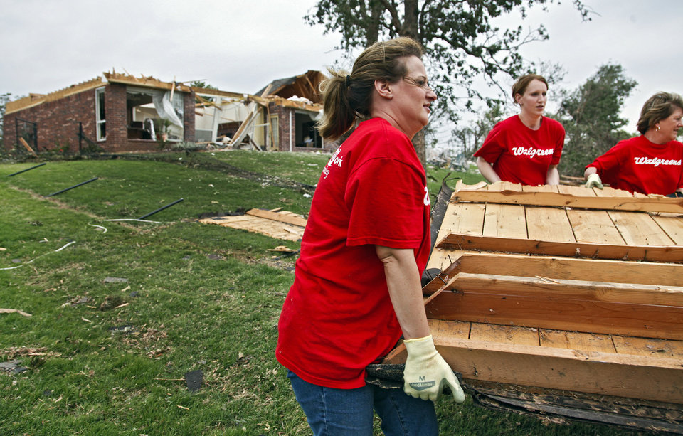 Photo -  Walgreens volunteers Michelle Cue, Tracey Sonka and Debbie Eastland, from left, work to clean up debris and damage on Wednesday, May 12, 2010, in Oklahoma City, Okla. left behind by the tornados that hit central oklahoma on Monday. Photo by Chris Landsberger, The Oklahoman