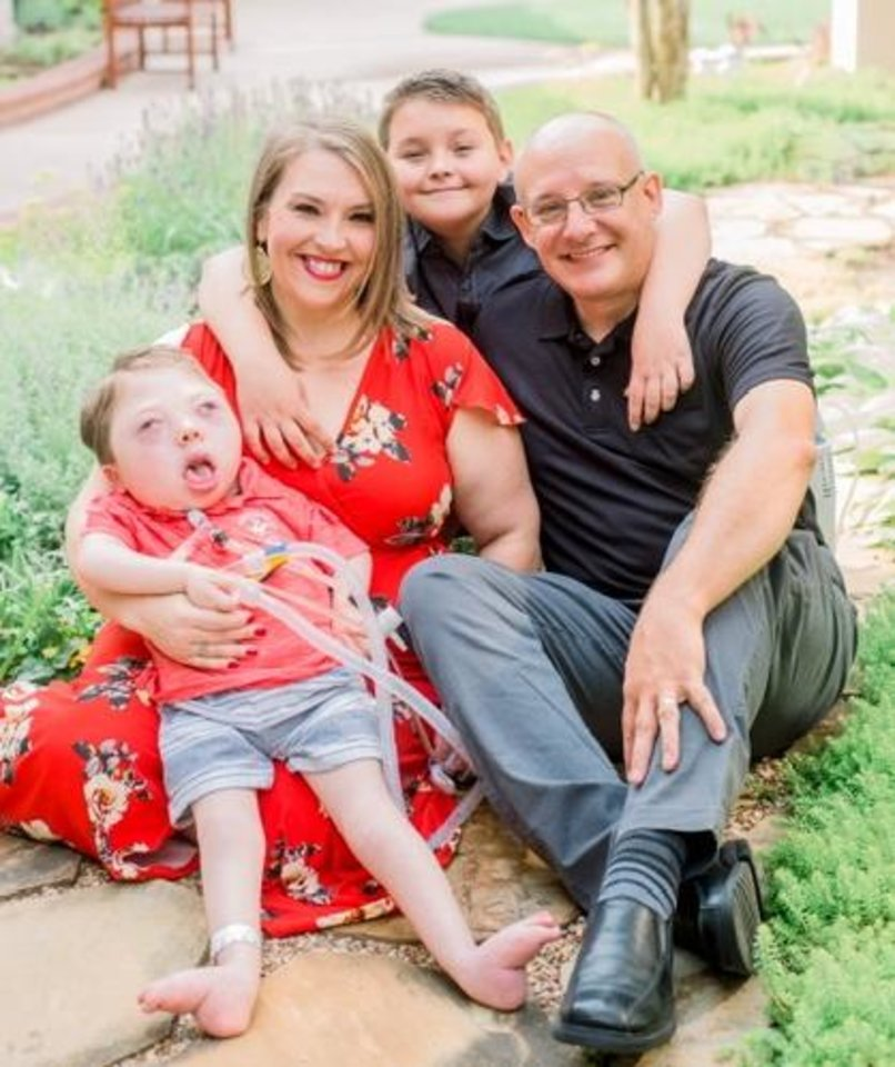 Photo - Cohen Grant's mother, Kim, holds him in this family photo with his brother, Carson, and father, Kyle. [PROVIDED]