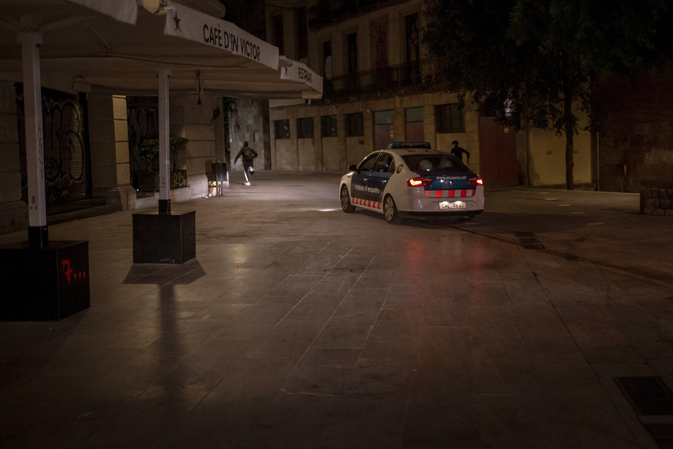 Photo -  People run away from police chasing them after curfew in Barcelona, Spain, Sunday, Nov. 1, 2020. On the strike of 10:00 p.m. crime fighters become party poopers in Barcelona. Police officers fan out across the Spanish city each night to stamp out clandestine parties that are prime contagion sources now that a nationwide curfew has shut down bars and nightclubs. (AP Photo/Emilio Morenatti)