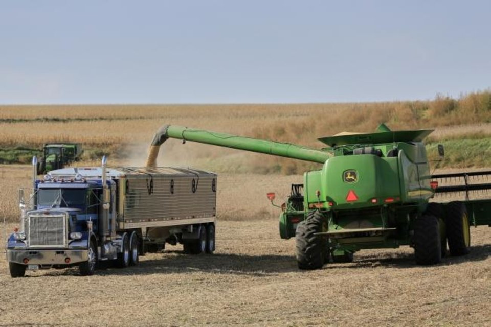 Photo -  A combine loads soybeans into a grain truck in rural Blair, Neb. [AP PHOTO]