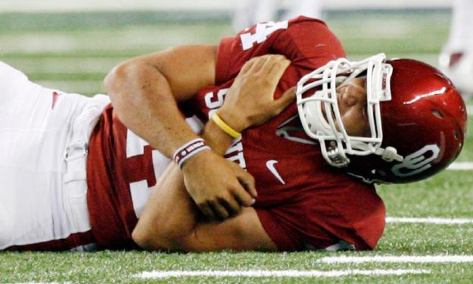 Photo - Oklahoma quarterback Sam Bradford went down in the second quarter with an apparent shoulder injury. PHOTO BY NATE BILLINGS, THE OKLAHOMAN
