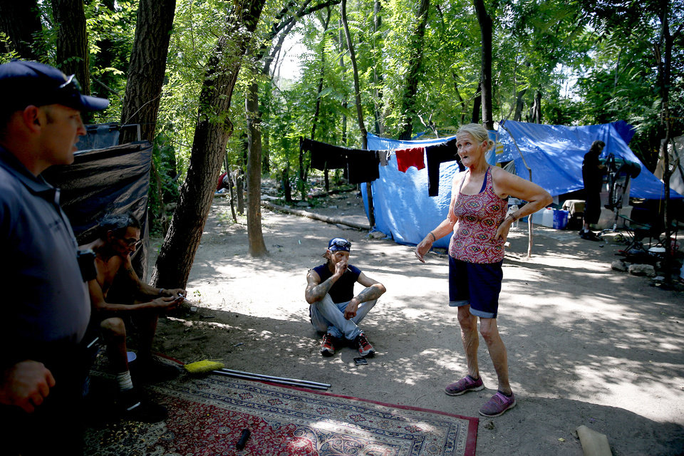 Photo -  Frances Cedartree talks July 10 with officer Felix Valadez with the Oklahoma City Police Department's Homeless Outreach Team at a camp just west of downtown Oklahoma City where she and others live. [Photo by Bryan Terry, The Oklahoman]