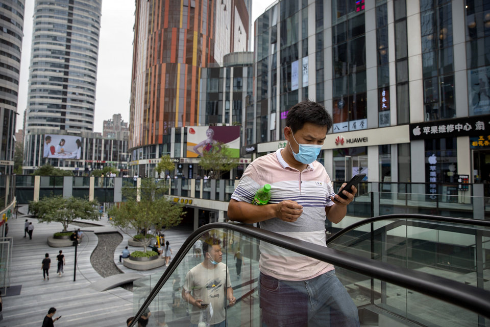 Photo -  A man wearing a face mask to protect against the spread of the new coronavirus rides an escalator at a shopping and office complex in Beijing, Wednesday, June 24, 2020. New virus cases have declined in China and in the capital Beijing, where a two-week spike appears to be firmly waning. (AP Photo/Mark Schiefelbein)