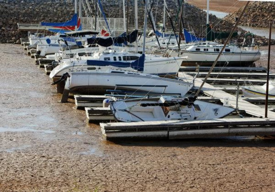Photo - Officials are releasing water from Canton Lake to replenish Lake Hefner and Lake Overholser in Oklahoma City. These boats on Hefner's east side are shown resting in mud last week because of low water levels caused by the drought.  NATE BILLINGS - The Oklahoman