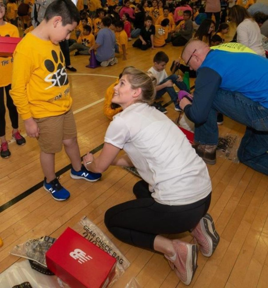 Photo -  Volunteers help fit students with running shoes. The Oklahoma City Memorial Kids Marathon recently teamed up with Oklahoma Cleats for Kids to provide new running shoes to the entire running club at Santa Fe South Elementary School. [PHOTO PROVIDED]